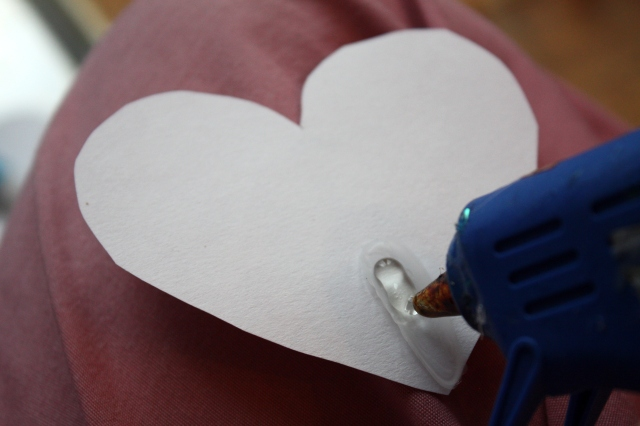 Use a hot glue gun to affix the party horn to the back of the heart.  It holds MUCH better than white glue.
